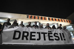 Mourners held a banner demanding justice.   Photo: Atdhe Mulla