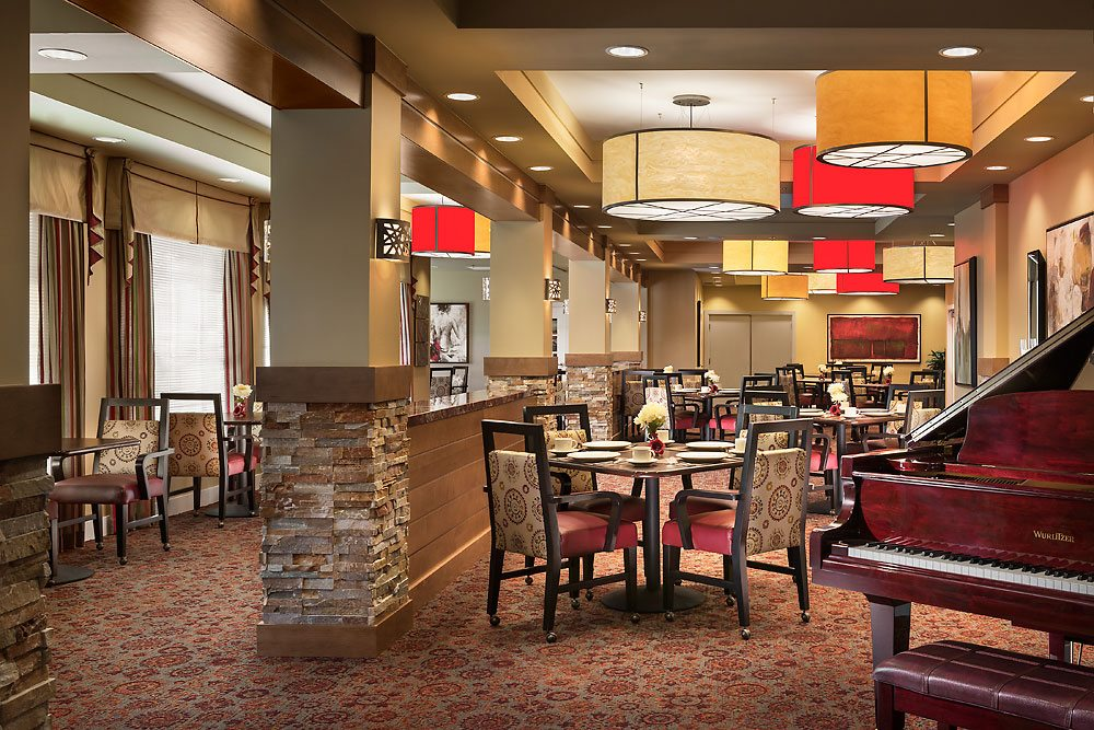 Lower ceilings and softer surfaces like carpet and curtains, such as these in a Glendale, Arizona MorningStar senior living community, help capture and absorb sound for a better dining experience. Photo credit: Mark Boisclair Photography