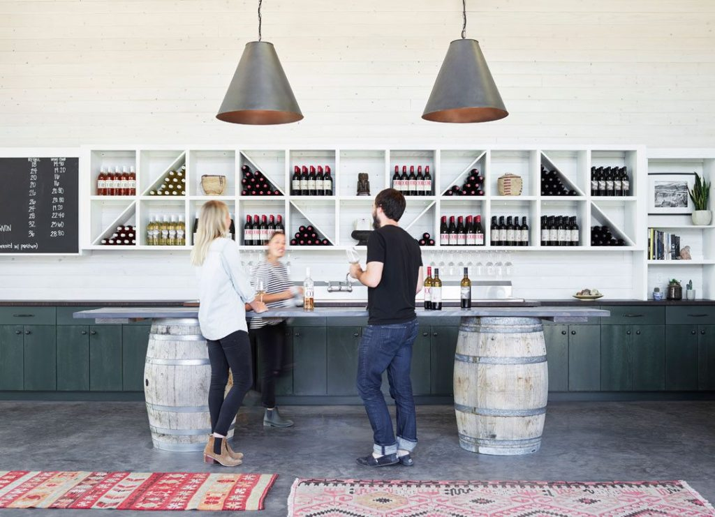 The tasting room bar draws visitors through the courtyard displaying all of the current wines. Photographer: Kevin Scott