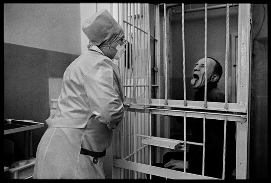 Correctional Treatment Unit #1, a TB prison colony in Tomsk, Siberia. A prisoner proves to a nurse that he has swallowed his daily oral TB medication. The prisoners receive treatment through metal bars in order to give security to the nurses. Treatment is supervised by Partners in Health in partnership with the government TB program.