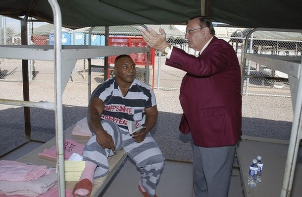 """Former world heavyweight boxing champion Mike Tyson listens to Sheriff Joe Arpaio (R) in the tent Tyson will stay in for 24 hours at  Maricopa County Jail's tent city for prisoners in Phoenix, Arizona November 20, 2007. Tyson was sentenced on Monday to three years probation and one day in jail for drug possession and driving under the influence. Tyson is holding a copy of the book """"American Gangster""""  according to Maricopa County Sheriff Joe Arpaio. REUTERS/Photo Courtesy of Maricopa County Sheriffs Department/Handout"""