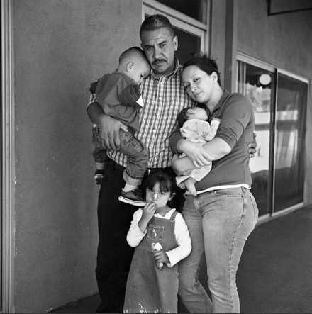 """© Joseph Rodriguez. """"Jorge Carbajal, 41 years old comes to Walden House for parenting classes and to help his wife Elizabeth and their kids. Here they are all together for their first family portrait in years. He quit his job with the airline KLM which had him traveling all over the world. Jorge says, """"I had to help my wife who has a drug addiction problem and I did not want to see my kids wind up in the system."""" He is a rare individual as he was the only regular father/husband that I got to know who came regularly to meetings."""" Joseph Rodriguez"""