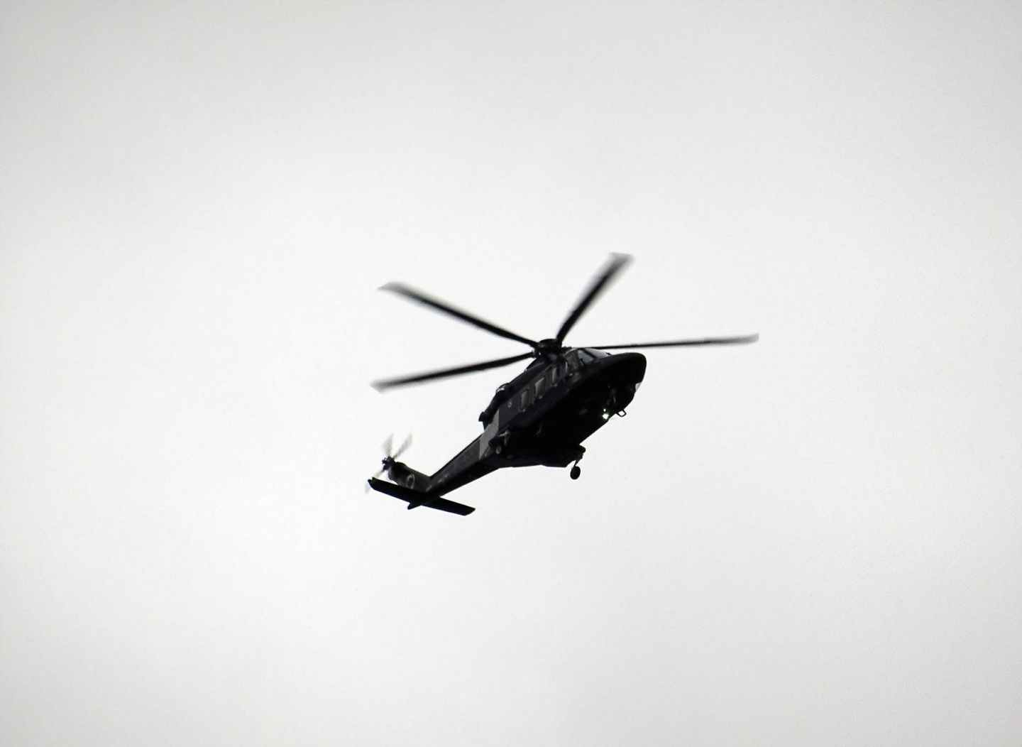 monochrome photo of flying helicopter