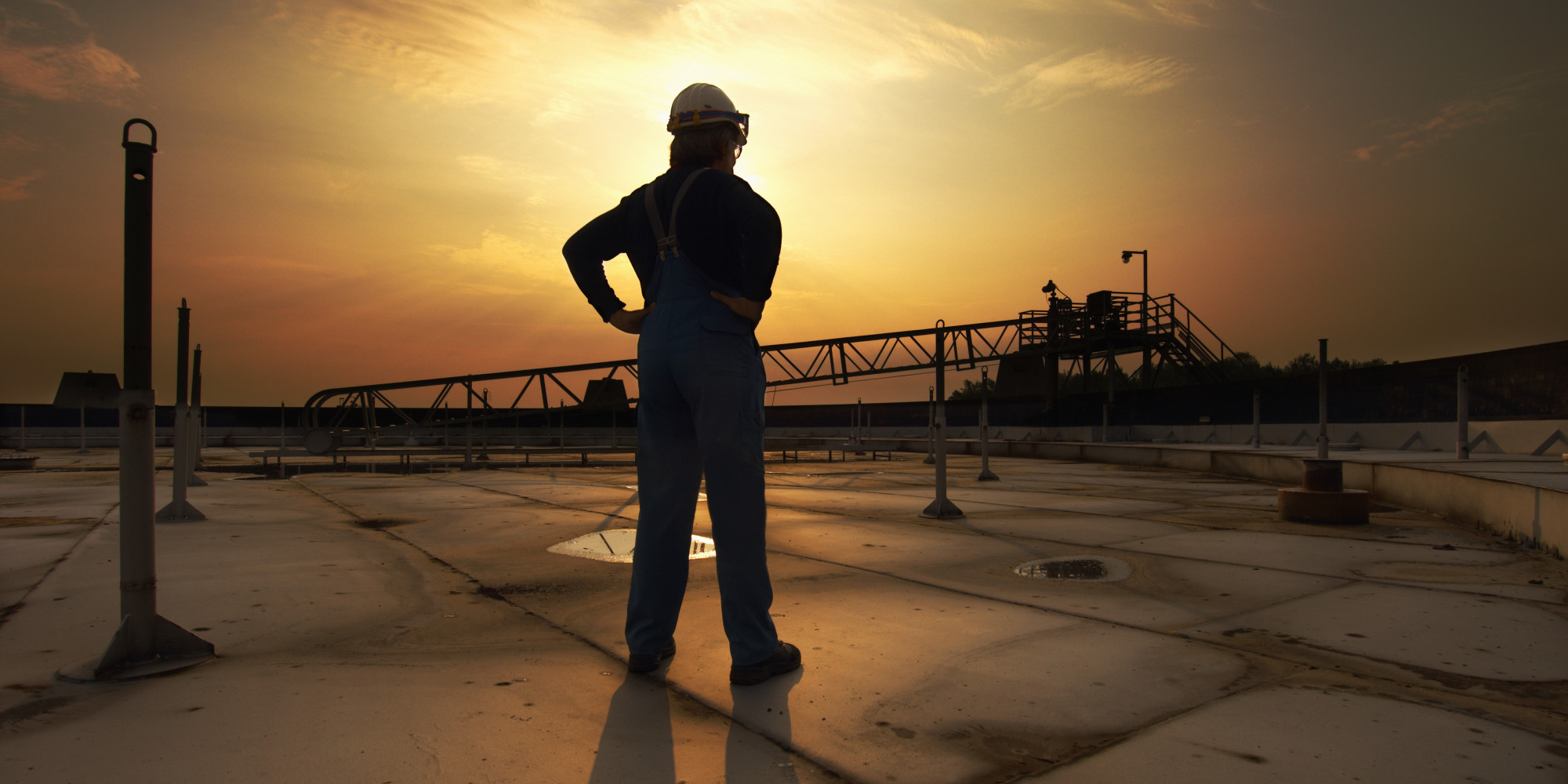 Man In Safety Clothing Standing On Top Of Oil Tank At Sunrise Rear View