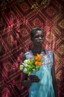 Alexia Webster, Nyaloki Mayor, 13, holds flowers in a United Nations IDP camp in Juba, South Sudan. 2016