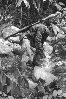 Serrania de San Lucas-Boliviar. A guerlla from the ELN (the National Liberation Army) rests on the shores of the Santo Domingo river.  Since 1986...