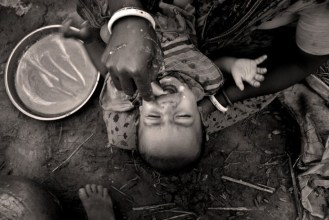 A mother is feeding her child as they move towards a new land.