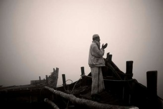 Aged 65, Aiyub Ali rises early to pray before a full day loading the boat with Golpata.