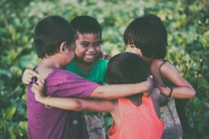 4 young children in a group hug with smiling faces.