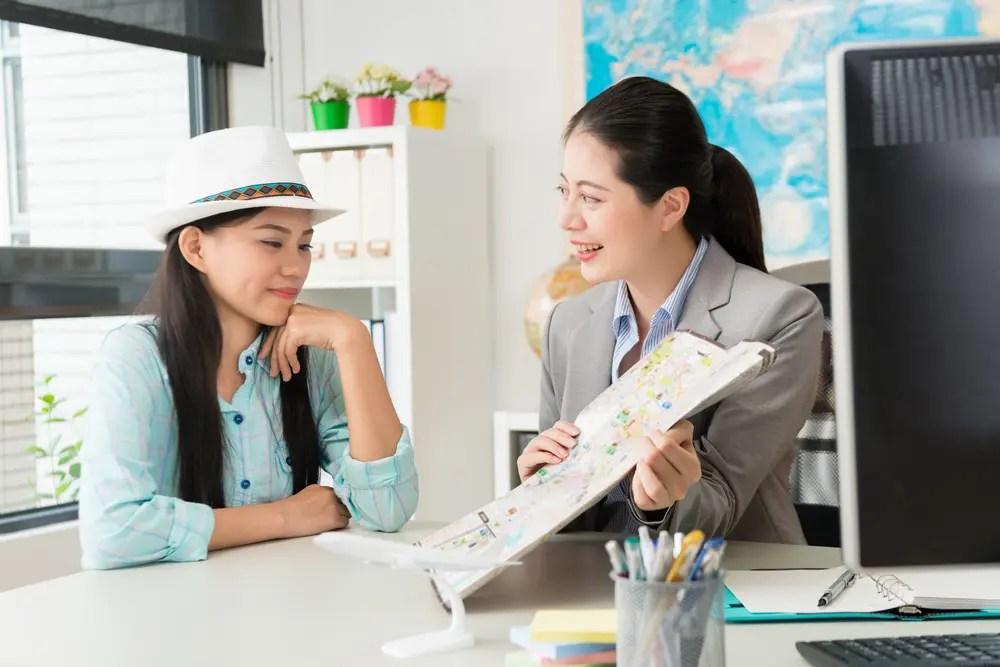 資格を持った旅行代理店店員がお客さんにプランを案内している