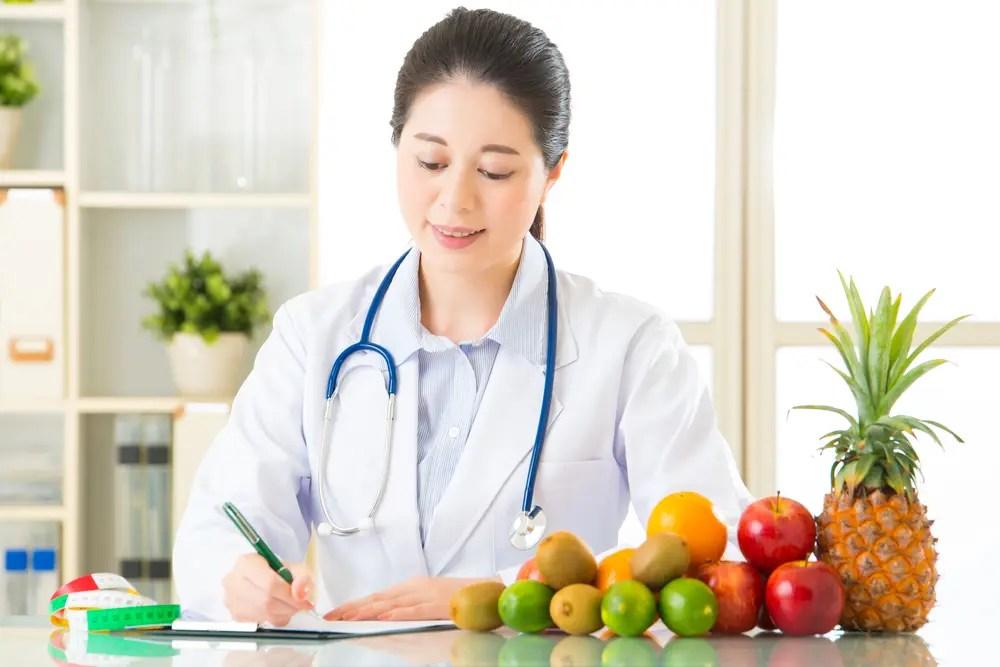 果物に関する栄養指導の書類を作成する管理栄養士の女性