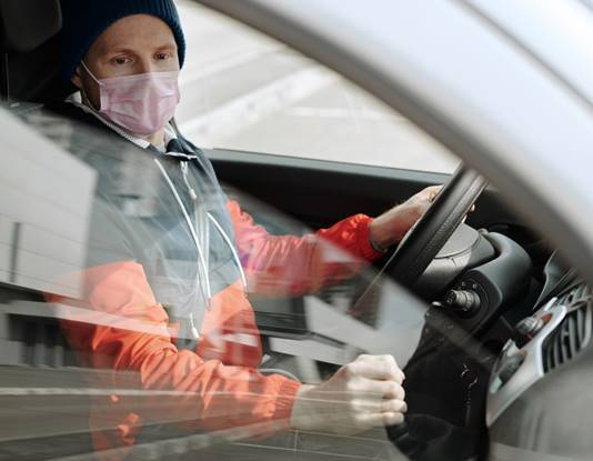 man driving car while wearing a mask