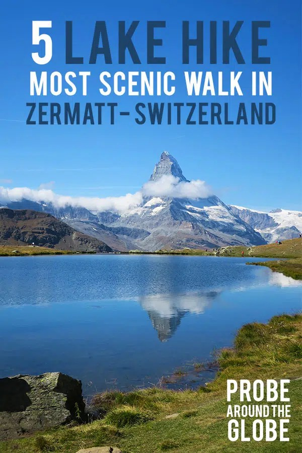Scenic image of the Matterhorn mountain reflected in the water of Stellisee Switzerland under a clear blue sky with some small clouds. Text overlay saying: 5-Lake Hike Most scenic walk in Zermatt Switzerland. Probe around the Globe