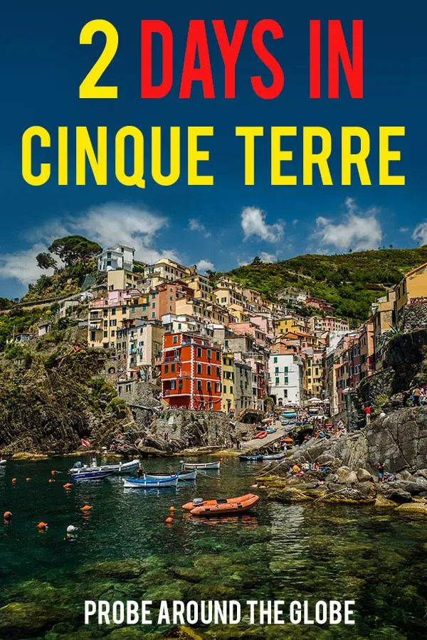 Colorful houses stacked together on a small cliff with a harbor in front of it with little blue and white boats. Blue sky with text overlay saying 2 days in Cinque Terre Italy Probe around the Globe.
