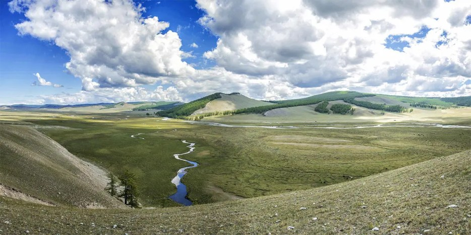 Green steppe with a meandering river leading into the mountains in the distance with a bright blue sky and looming white clouds above the scenery in Mongolia.