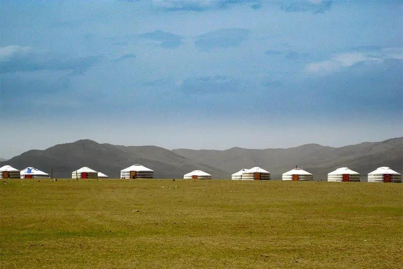 White round tents in a sea of green grass against a backdrop of purple grey mountains and bright blue sky in Mongolia.