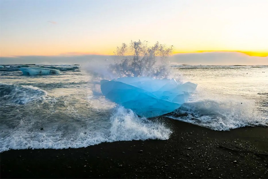 Black sand beach with blue ice block. Waves crashing onto the ice block at sunset.