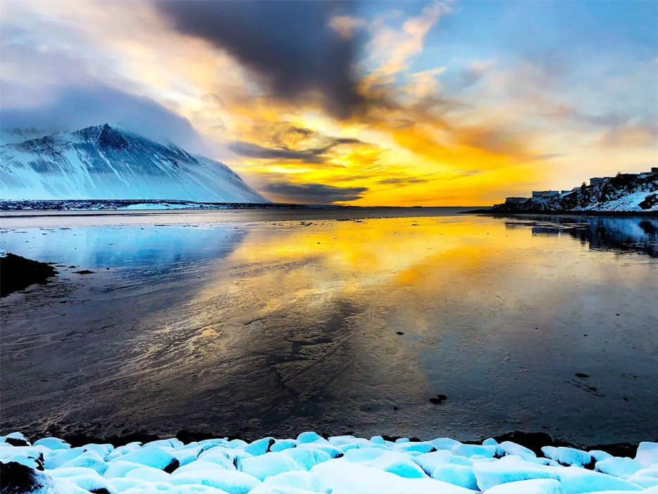 Frozen lake with black ice and black, snow covered mountains surrounding the lake. Above the lake, a dark clouds continues into a bright yellow sunrise. The colors of the sunrise are reflected on the ice.