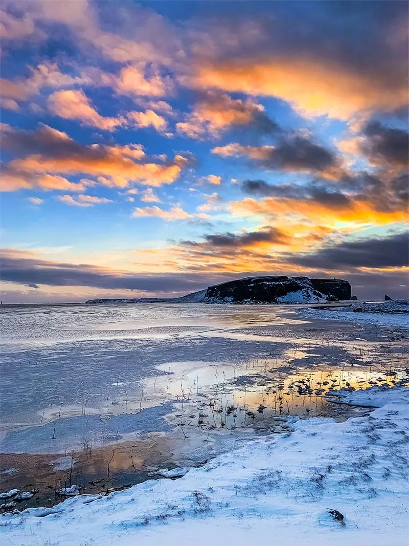 Snow-covered ground with frozen water and black mountains in the distance. Cloudy sky with orange and black clouds, colored by the sunrise.