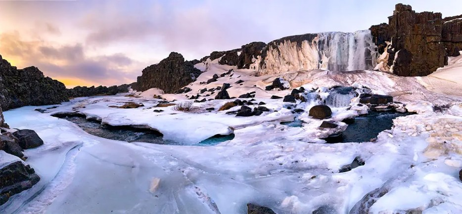 Panoramic sunrise image of snow-covered Oxararfoss Waterfall in Iceland in Winter