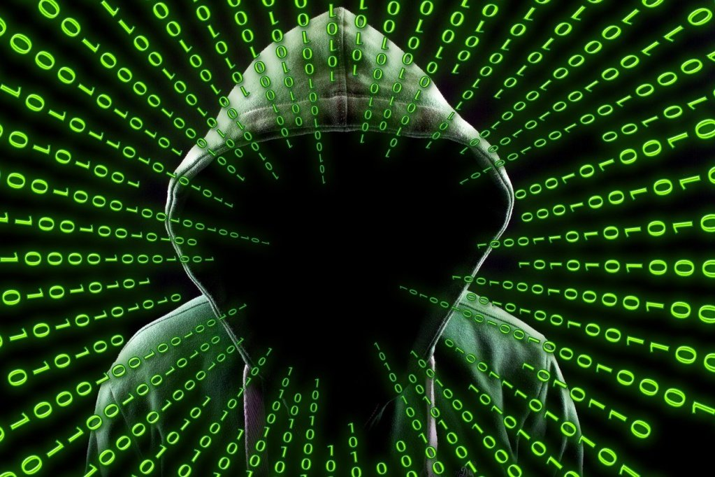 A hooded person with their face hidden, surrounded by a field of green ones and zeroes. Antivirus can help keep hackers at bay!