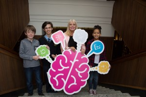 Minister Mitchell O'Connor pictured with students holding speech bubbles with colourful language symbols