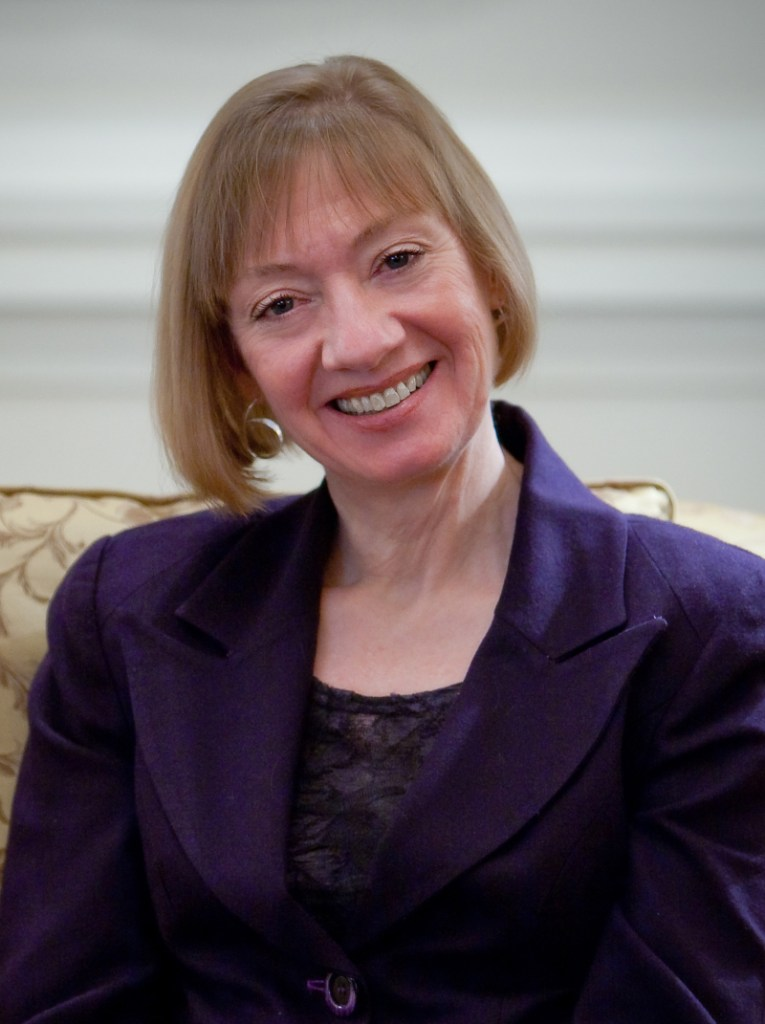 Nina E. Olson smiling, wearing a purple suit.