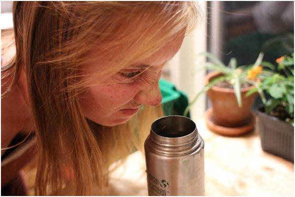 Girl sniffing thermos.