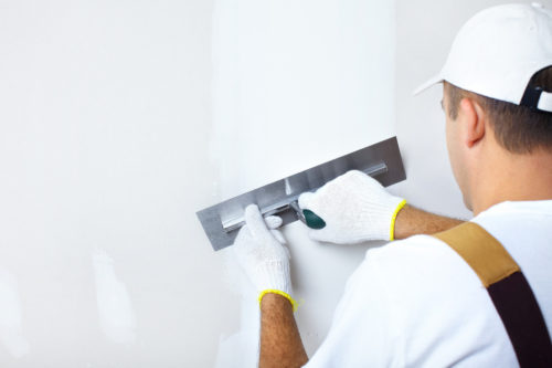 man smoothing out plaster on the wall