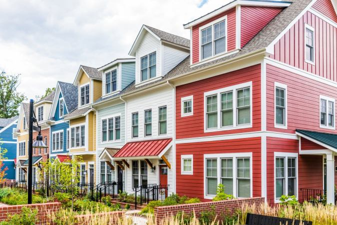 Row of multicolored painted townhomes under a cloudy sky. Determine when to repaint your house by clicking the photo