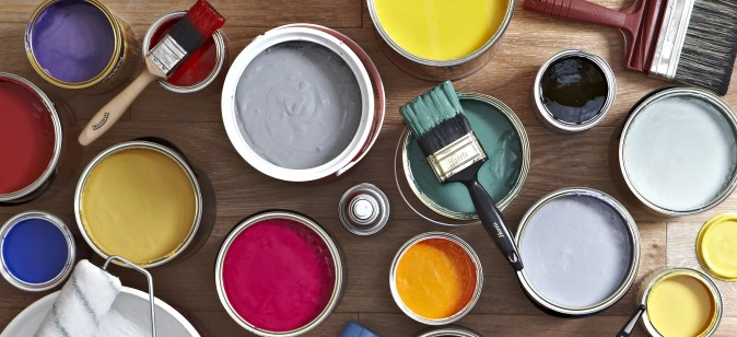 areal view of open multi sized paint cans with two paint brushes on top of two cans