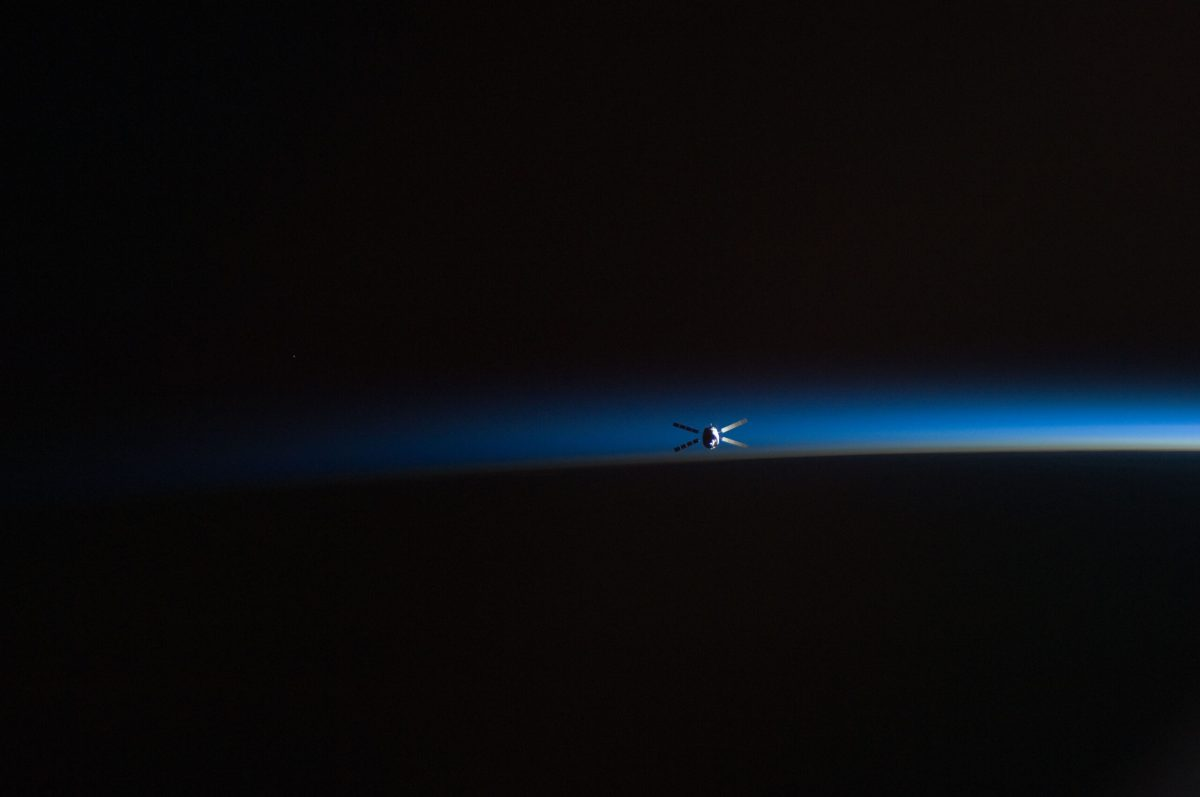 The Kepler spacecraft above the horizon of Earth in orbit. A stripe of light blue separates a dark planet from the dark sky.