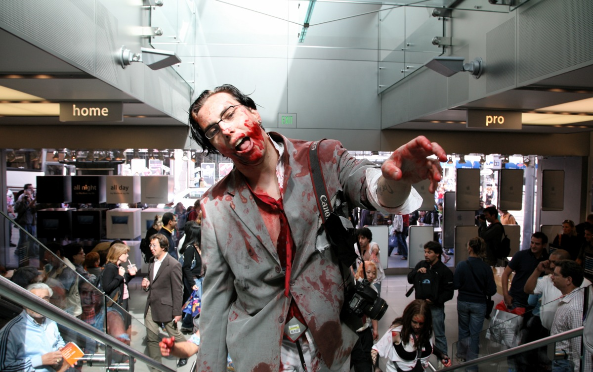 A man in zombie cosplay on the stairs at the San Francisco Apple Store, which is quite busy.