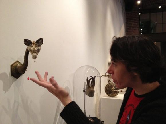 España extending a hand to a piece of art reminiscent of a shrunken cat's head on the wall at an art gallery.