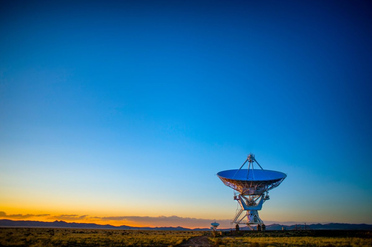 An image of several radio telescope dishes from the Very Large Array against a very blue sky with orangey sunlight just above the horizon.
