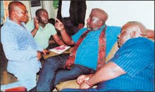 Two Imo lawmakers, Stan Dara and Ike Amuka kneeling before Okorocha in Govt. House, Owerri