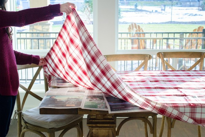 Protect a wood table from spills by setting down newspaper underneath a tablecloth.