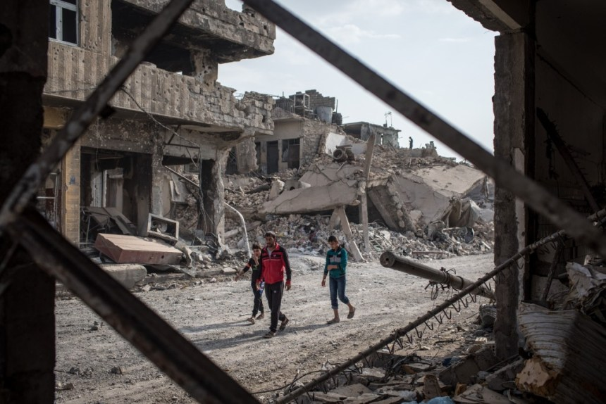 MOSUL, IRAQ - NOVEMBER 06: People walk amongst rubble from destroyed buildings in an outer neighborhood of the Old City in West Mosul on November 6, 2017 in Mosul, Iraq. Five months after Mosul, Iraq's second-largest city was liberated from ISIL in a nine-month long battle, residents have returned to the destroyed city to rebuild their lives. After more than two years of ISIL occupation, savage fighting, airstrikes and as ISIL fighters retreated they intentionally destroyed remaining key infrastructure such as bridges, government buildings, water and sewage facilities and neighborhoods laced with booby traps and homemade bombs leaving the city in ruins. Despite the damage residents have hastily returned and managed to setup temporary shops, homes and services to help bring the city back to life. In West Mosul, home to the Old City, more than 32,000 homes were destroyed and a recent report from the U.N. estimates repairing Mosul's basic infrastructure will cost more than $1 billion and take years to complete. (Photo by Chris McGrath/Getty Images)