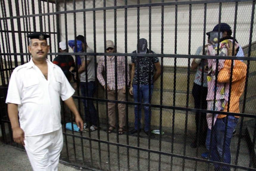"""CAIRO, EGYPT - NOVEMBER 01: Eight people sentenced to three years in jail after joining an illegal gay wedding ceremony are seen behind the bars in Cairo, Egypt, on November 1, 2014. The men were found guilty of spreading """"indecent images"""" and """"inciting debauchery"""" over a video that appeared to show them celebrating a gay marriage in Cairo. (Photo by Stringer/Anadolu Agency/Getty Images)"""