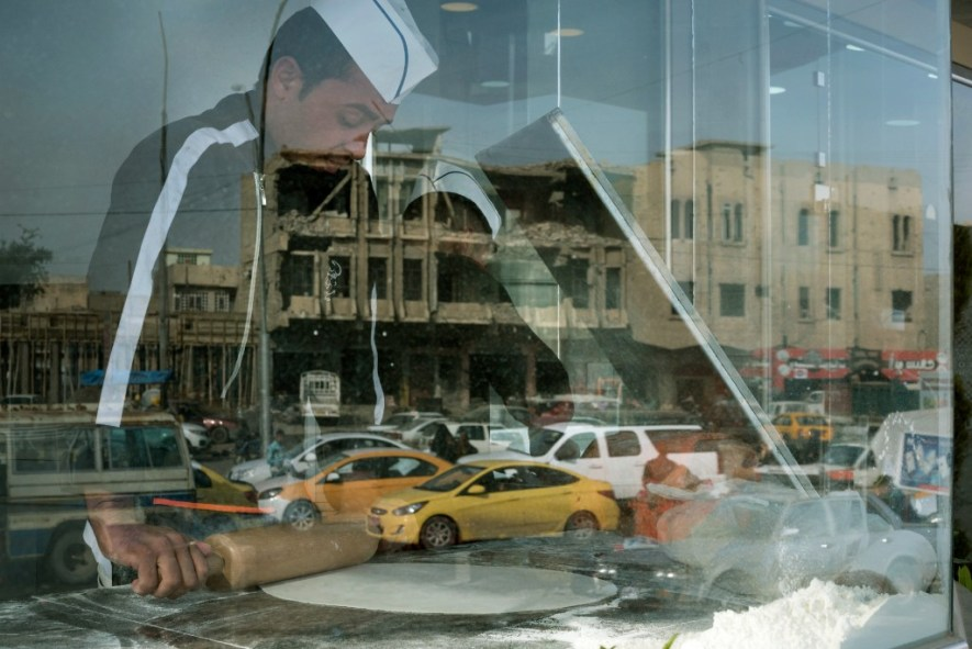 A damaged building is seen in the reflection of a bakery window in Mosul's al-Jadidah district.