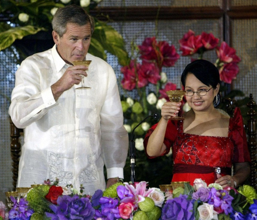 MANILA, PHILIPPINES:  US President George W. Bush (L) toasts with Philippine President Gloria Macapagal Arroyo at the Malacanang Palace in Manila, 18 October 2003, during his State Visit to the Philippines as part of his 9-day trip in Asia.  President Bush on 18 October pledged funds and training to help the Philippines military quash regional extremists as he made an eight hour state visit to this staunch war-on-terrorism ally.    AFP Photo/Paul J. RICHARDS  (Photo credit should read PAUL J.RICHARDS/AFP/Getty Images)