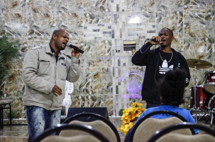 Imigrantes africanos participam de cerimônia na igreja Ministry of the World of Fire.