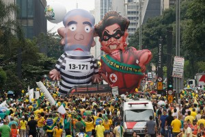 Demonstrators parade large inflatable dolls depicting Brazil's former President Luiz Inacio Lula da Silva in prison garb and current President Dilma Rousseff dressed as a thief, with a presidential sash that reads