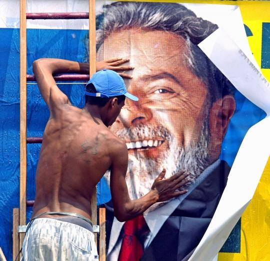 SAO PAULO, BRAZIL: A worker puts up a campaign sign for Brazilian presidential candidate Luiz Inacio Lula da Silva, of theWorkers Party, (PT) 24 October, 2002, in Sao Paulo, Brazil. Lula heads to the 27 October second round of voting with 65 percent support and a massive lead over the ruling party's Jose Serra. AFP PHOTO/Mauricio LIMA Un trabajador pega un afiche con la imagen de Luiz Inacio Lula da Silva, candidato opositor del Partido de los Trabajadores (PT) a la presidencia de Brasil, el 24 de octubre de 2002, en Sao Paulo, Brasil. Segun sondeos Lula, obtendria del 66% de las intenciones de voto para el balotaje del 27 de octubre, mientras que Jose Serra, del Partido de la Social Democracia Brasilena (PSDB), obtendria el 34%. AFP PHOTO/Mauricio LIMA (Photo credit should read MAURICIO LIMA/AFP/Getty Images)