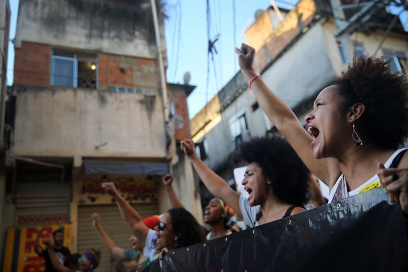 RIO DE JANEIRO, BRAZIL - AUGUST 22: Demonstrators march through the Manguinhos favela to protest against police killings of blacks on August 22, 2014 in Rio de Janeiro, Brazil. Every year, Brazil's police are responsible for around 2,000 deaths, one of the highest rates in the world. Many of the deaths in Rio involve blacks killed in favelas, also known as slums. (Photo by Mario Tama/Getty Images)