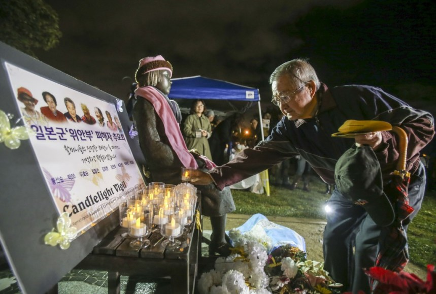 """A supporter offers flowers to a memorial statue honoring """"Comfort Women"""" at Glendale Peace Monument  during a candlelight vigil in remembrance and support of """"Comfort Women"""", Japanese military sexual slavery victims during World War II, on January 5, 2016, in Glendale, California. AFP PHOTO / Ringo Chiu / AFP / RINGO CHIU        (Photo credit should read RINGO CHIU/AFP/Getty Images)"""