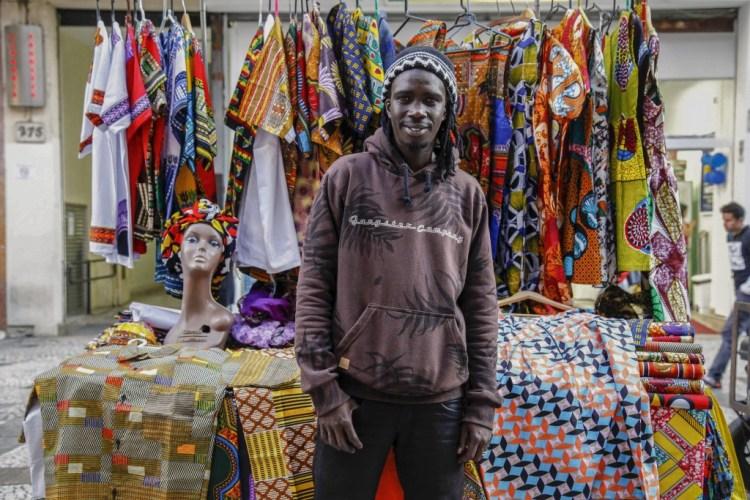 O refugiado senegalês Abu vende roupas costuradas com tecidos típicos em uma barraca no Praça da República, em São Paulo.