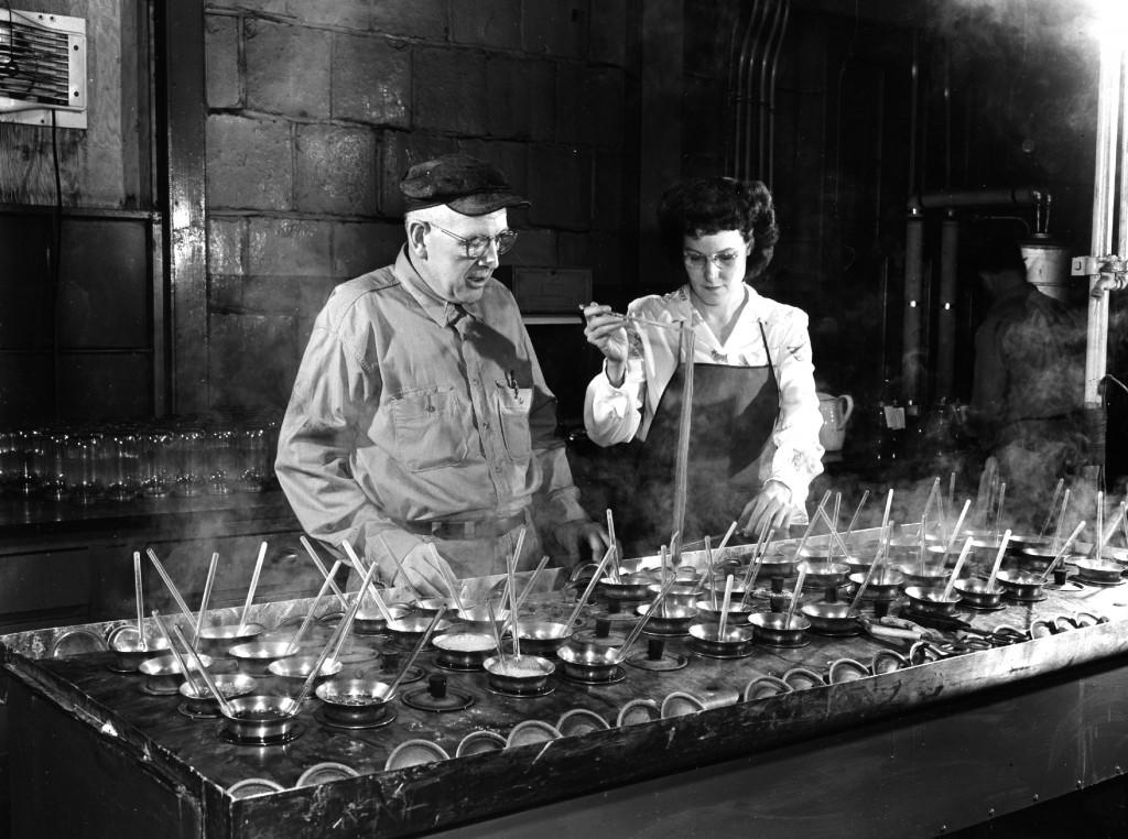 Um fabricante de corantes especializado no Departamento de Produtos Químicos Orgânicos Chambers Works da DuPont em Deepwater Point, Nova Jersey, acompanhado de um técnico de laboratório, verificando tonalidades de corantes nos anos 1950.