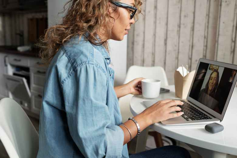 woman in blue denim jacket using macbook pro