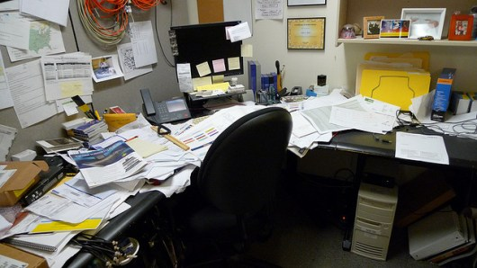 Messy freelance writer's desk in a home office.